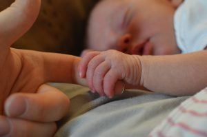 A sleeping baby holding their parent's finger